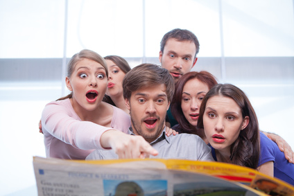 Group of young people reading newspaper. Looking very surprised and interested in