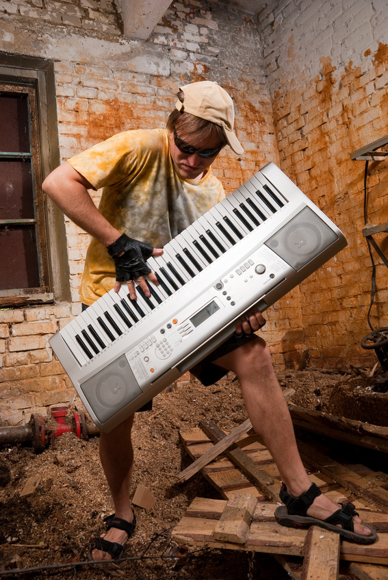 Musician plays a synthesizer in abandoned industrial interior