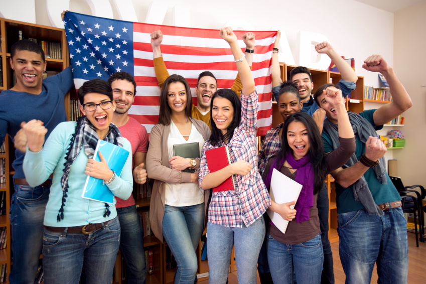 Smiling American students presenting their country with flags