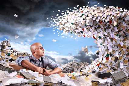 Castaway businessman in a sea of papers and files