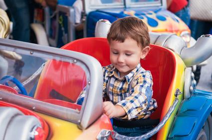 Little boy riding a car in amusement park