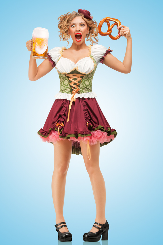 Young sexy Oktoberfest waitress wearing a traditional Bavarian dress dirndl holding a pretzel and beer mug, and laughing happily on blue background.