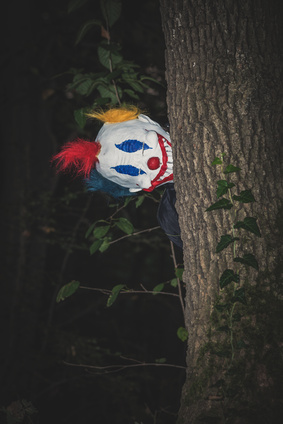 scary clown behind tree in park night scene